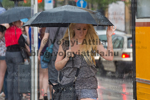 Woman holds an umbrella during a rain shower in central Budapest, Hungary on May 03, 2013. ATTILA VOLGYI