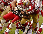 San Francisco 49ers linebacker Julian Peterson (98) tackles Kansas City Chiefs running back Priest Holmes (31) on Sunday, November 10, 2002, in San Francisco, California. The 49ers defeated the Chiefs 17-13.