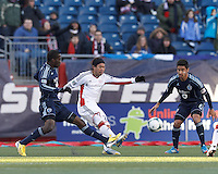 New England Revolution midfielder Lee Nguyen (24) crosses the ball as Sporting Kansas City midfielder C.J. Sapong (17) defends.  In a Major League Soccer (MLS) match, Sporting Kansas City (blue) tied the New England Revolution (white), 0-0, at Gillette Stadium on March 23, 2013.