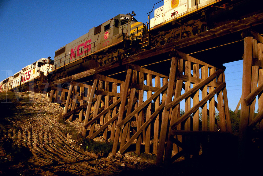Railroad locomotives pull a train across a bridge, or trestle.