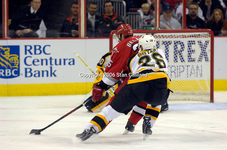 The Boston Bruins' Brad Boyes (26) tries to reach in as the Carolina Hurricanes' Eric Belanger, in red, races for the goal during an NHL hockey game Saturday, Dec. 2, 2006 in Raleigh, N.C. Carolina won 5-2.<br />