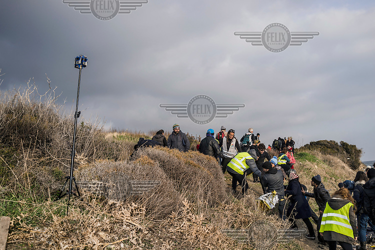 A media producer plants a virtual reality camera on the shoreline to record the refugees who have just landed.
