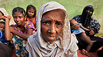 A Rohingya woman, having just crossed the border from Myanmar, waits with other members of her family to complete registration in the Kutupalong Refugee Camp near Cox's Bazar, Bangladesh. More than 600,000 Rohingya refugees have fled government-sanctioned violence in Myanmar for safety in this and other camps in Bangladesh.