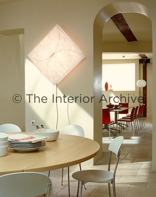 Contemporary Italian furniture has been used in this tiled basement kitchen/dining area