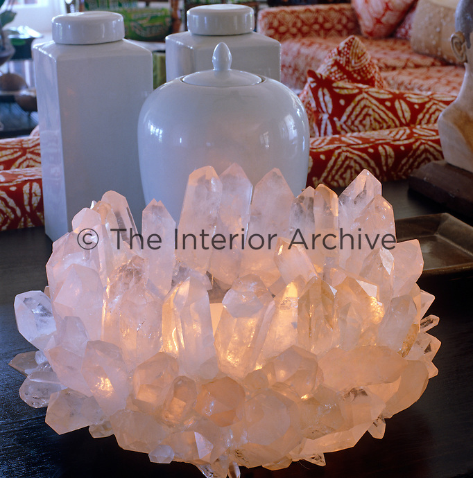 A candle glows from the centre of a Californian crystal on an Indonesian table in the living room