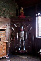 An armour display in the New Gallery. An example of William Morris wallpaper can be seen on the left