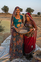(L-R) Guar farmers Kelavati Devi, 38, and her relative Manju Sankaram pose for a portrait holding guar beans after threshing the crop in their shared field in Rajera village, Bikaner, Rajasthan, India on October 23, 2016. Non-profit organisation Technoserve works with farmers in Bikaner, providing technical support and training, causing increased yield from implementation of good agricultural practices as well as a switch to using better grains better suited to the given climate. Photograph by Suzanne Lee for Technoserve