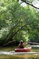 Rear view of a woman canoeing on the Eyre river, Aquitaine, France.