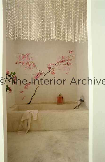 A mural of a cherry tree in bloom has been painted on one wall of this simple bathroom
