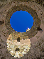Diocletian's Palace is an old Roman ruin in Split Croatia.  This is a domeed roof near the church.  A circle of sunlight forms the bottom of a figure eight along with a hole in the top of the domed roof.
