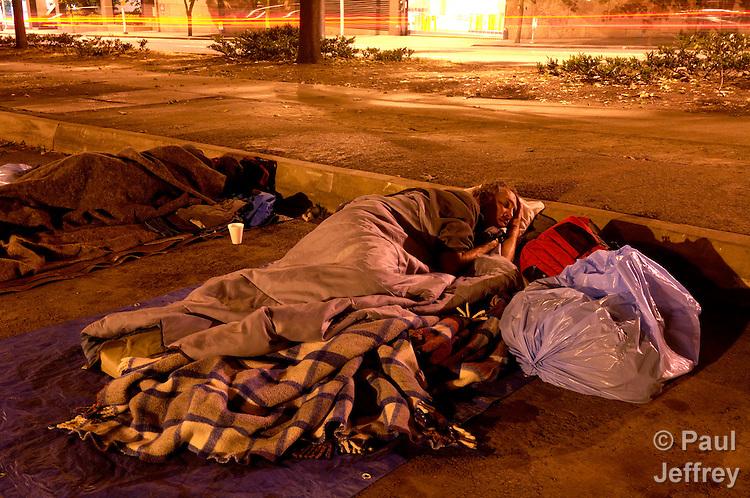 Homeless people sleep under a freeway in Seattle.
