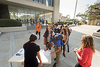 Occidental College students sign a petition after marching in a rally organized by Fossil Free Occidental on Nov. 14, 2014. The group hopes to end Oxy's reliance on fossil fuels by freezing all investments in the 200 largest fossil-fuel companies (measured by their proven carbon reserves in oil, gas or coal) and over the next five to ten years sell the stock in these same companies, and then reinvest 5%, at minimum, of the divested portfolio in socially responsible investments. (Photo by Marc Campos, Occidental College Photographer)