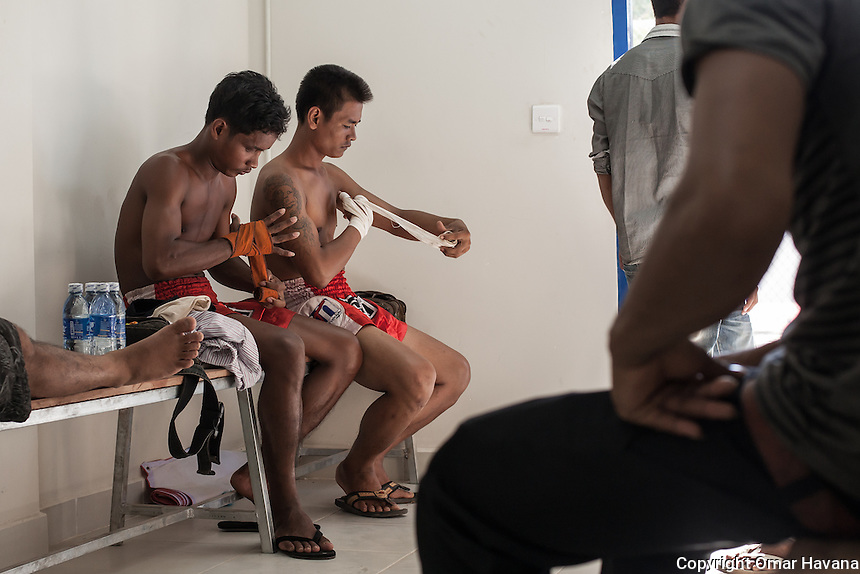 SIEM REAP, CAMBODIA. Two Kun Khmer fighters wrap their hands with ropes moments before his fight at the new Siem Reap arena in Cambodia. Pradal Serey or Kun Khmer -free fighting- is an unarmed martial art from Cambodia. Compared to other forms of Southeast Asian kickboxing, Kun Khmer emphasises more elusive and shifty fighting stances. The Cambodian style tends to utilise more elbows than that of other regions. Evidence shows that a style resembling pradal serey existed in the 9th century, leading the Khmer to believe all Southeast Asian forms of kickboxing started with the early Mon-Khmer people. They maintain that Pradal Serey has influenced much of the basis of Muay Thai. During the Khmer Rouge genocide, traditional martial arts were banned and many boxers were executed or worked to death, which nearly caused the death of pradal serey. Nowadays, Kun Khmer is making a strong comeback in Cambodia, with fighters attempting to market their style of boxing at the same caliber of Muay Thai. Photography: ©Omar Havana