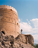 OMAN, Muscat, man looking through a pair of binoculars by fort, low angle view