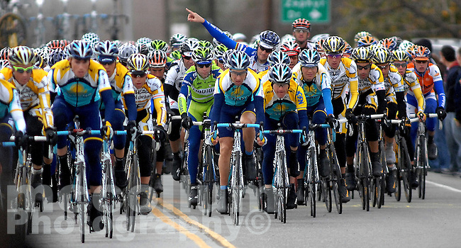 The pack of cyclists , with one saluting the crowd, makes it's way down West Linne Road Road in Tracy during the Amgen Tour of California Tuesday afternoon.