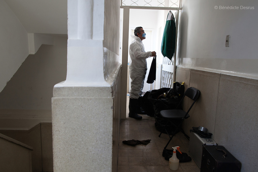 "Donovan puts on his Hazmat suit before beginning a forensic cleaning in Mexico City, Mexico on January 14, 2016. The decomposed body of a man in his 50s was found on the floor of his mother's bedroom, days after he had died of an intestinal obstruction. Because of her physical disability, the mother of the deceased – who had been her caregiver – was unable to move enough to make an emergency call. As a consequence, she was trapped in the room for three days with the body of her son – and without food or water - before help arrived. Donovan Tavera, 43, is the director of ""Limpieza Forense México"", the country's first and so far the only government-accredited forensic cleaning company. Since 2000, Tavera, a self-taught forensic technician, and his family have offered services to clean up homicides, unattended death, suicides, the homes of compulsive hoarders and houses destroyed by fire or flooding. Despite rising violence that has left 70,000 people dead and 23,000 disappeared since 2006, Mexico has only one certified forensic cleaner. As a consequence, the biological hazards associated with crime scenes are going unchecked all around the country. Photo by Bénédicte Desrus"