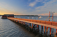 Historic Coupeville Wharf on Penn Cove, highlighted by sunset light with Mt. Baker in the distance. Coupeville, Ebey's Landing National Historical Reserve, Whidbey Island, Washington State.