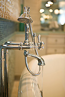 Polished chrome handheld mixer at soaking tub