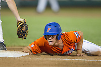 Florida Gators outfielder Harrison Bader (8) dives back to first base against the Virginia Cavaliers in Game 13 of the NCAA College World Series on June 20, 2015 at TD Ameritrade Park in Omaha, Nebraska. The Cavaliers beat the Gators 5-4. (Andrew Woolley/Four Seam Images)