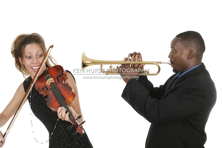 Two musicians play around with each other as they tune their instruments and prepare for a concert.