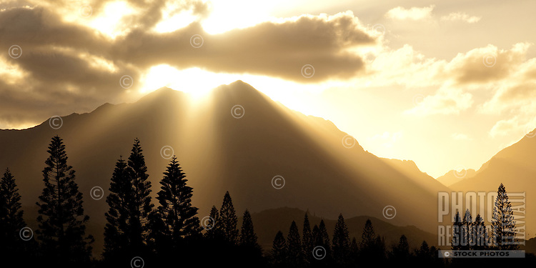 Rays of light shine through the clouds as the sun sets behind the Ko'olau Mountain Range in Kailua, O'ahu.