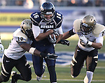 Idaho defenders Quin Ashley (12) and Bradley Njoku (23) tackle Nevada quarterback Tyler Lantrip, (16) after a 26-yard run in the third quarter of an NCAA football game in Reno, Nev., on Saturday, Dec. 3, 2011. Nevada won 5-3. .Photo by Cathleen Allison