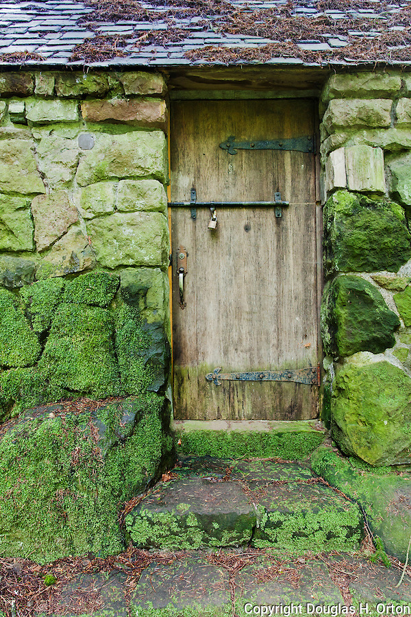 "Aging door in moss covered stone cabin deep in forest.  ""Portland's Secret Garden"",  Leach Garden was established by JOhn and Lilla Leach in the 1930's.  The Garden continues as a public place of respite and native northewest botanical display.  Operated by the city of Portland, Oregon.."
