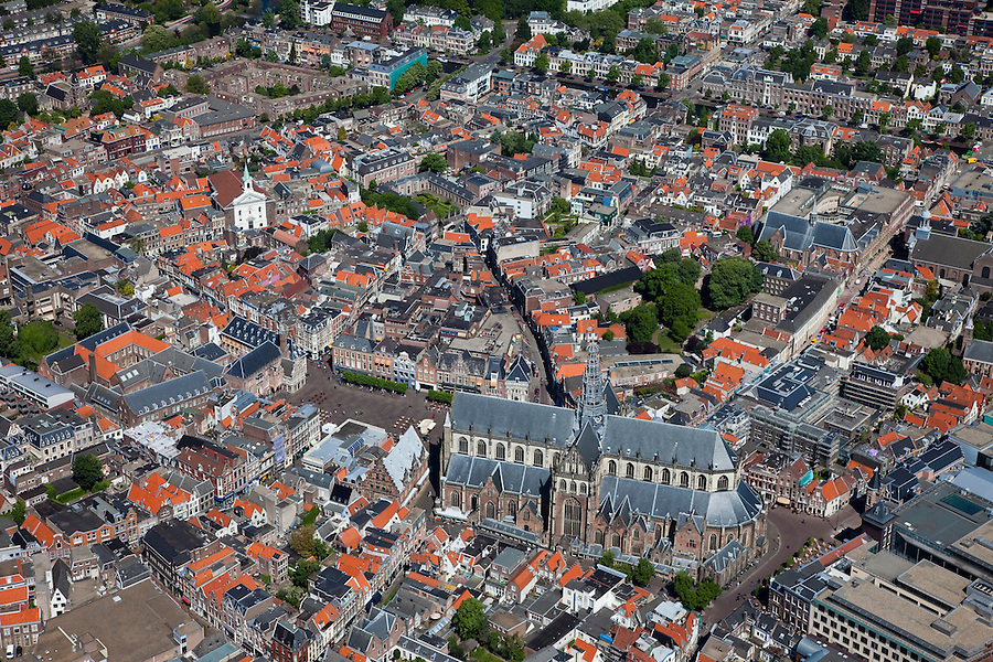 Nederland, Noord-Holland, Haarlem, 12-05-2009; overzicht van de stad met in het midden Grote Kerk of St. Bavokerk aan de grote Markt en het water van het Binnen Spaarne. In het midden, direkt onder de  St. Bavo, het nieuwe complex de Appelaar (voorheen drukkerij Enschede, nu onder andere Gerechtsgebouw, concertzaal, hotel), midden onder molen de Adriaan, midden recht Nieuwe Gracht. Aan de horizon de duinen van het Kennemerland met Zandvoort en de Noordzee.collectie, luchtfoto (toeslag); Swart Collection, aerial photo (additional fee required).foto Siebe Swart / photo Siebe Swart
