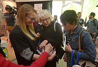 NWA Democrat-Gazette/BEN GOFF @NWABENGOFF<br /> Ruthie McRae (from right) of Fort Smith and JoAnne Mills of Little Rock take samples of nail polish from Lauren Sullivan, of Bentonville, with Coty Thursday, May 4, 2017, while walking through the Sponsor Village at Compton Gardens during the Bentonville Film Festival.