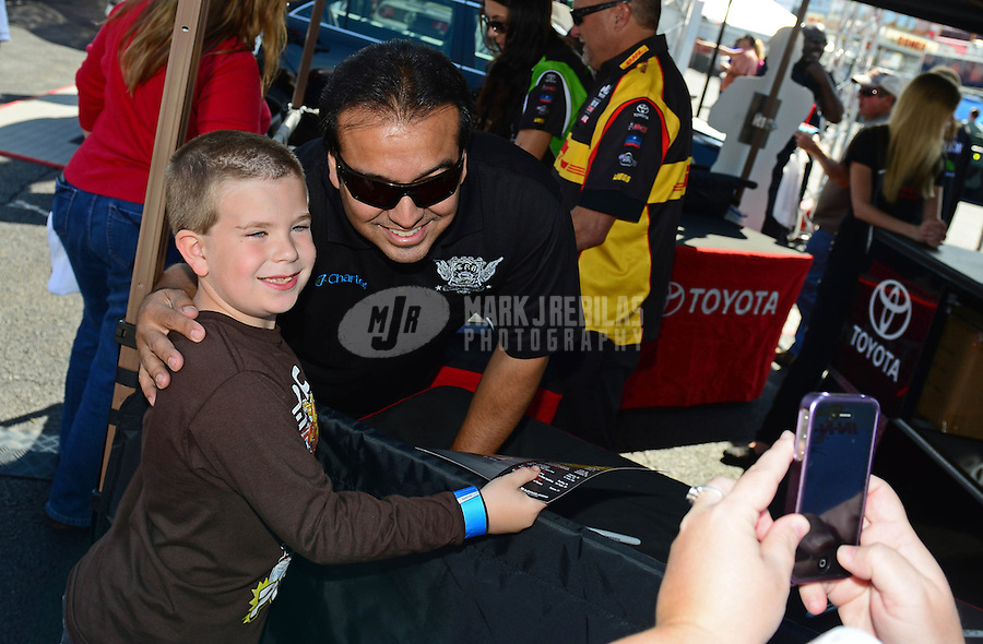 Sept. 28, 2012; Madison, IL, USA: NHRA funny car driver Tony Pedregon posses for a picture with a little fan during qualifying for the Midwest Nationals at Gateway Motorsports Park. Mandatory Credit: Mark J. Rebilas-