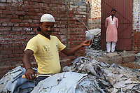 A man cuts and trims pieces of leather in a small, informal factory in the Jajmau area of Kanpur.