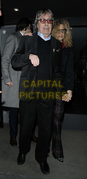 """Bill Wyman, Suzanne Wyman.attended the """"Bill Wyman : Reworked"""" private view, Rook & Raven, Rathbone Place, London, England..February 26th, 2013.full length black top jacket trousers tinted glasses sunglasses shades married husband wife hand arm.CAP/CAN.©Can Nguyen/Capital Pictures."""