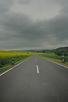 Empty country road on a grey cloudy day with hills in the back ground. Yellow oil seed rape crop on the left open countryside and homes on the right. Aschaffenburg area, Bavaria, Germany.