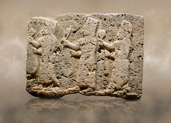 Photo of Hittite monumental relief sculpted orthostat stone panel of a Procession Limestone, Karkamıs, (Kargamıs), Carchemish (Karkemish), 900-700 B.C. Anatolian Civilisations Museum, Ankara, Turkey.<br /> <br /> It is a depiction of three marching female figures in long dress with a high headdress at their head. These women are considered to be the nuns of the Goddess Kubaba. The figures in the front and behind have a round mirror in their right hand while the figure in the middle has a bunch of spica in her right hand. Figures carry objects similar to a sceptre in their left hand.  <br /> <br /> Against a brown art background.