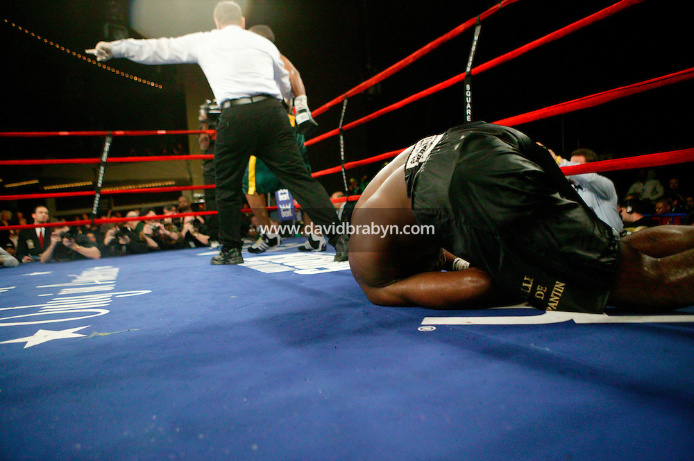 7 January 2006 - New York City, NY - As Frenchman Jean-Marc Mormeck (R, foreground) collapses knocked out, the referee sends Jamaican O'Neill Bell (hidden, green and yellow trunks) to the opposite corner during the World Cruiserweight Championship unification fight at Madison Square Garden in New York City, USA, 7 January 2006. O'Neil Bell won by KO in the 10th round.