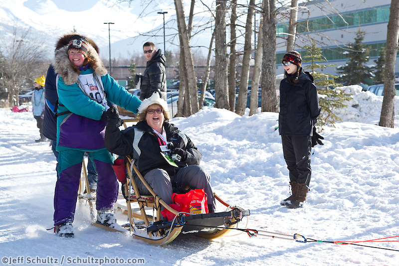 Angie Taggart and team run past spectators on the bike/ski trail during the Anchorage ceremonial start during the 2013 Iditarod race.    Photo by Britt Coon/IditarodPhotos.com