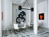 Dining tables by Angelo Mangiarotti are paired with Garouste and Bonetti wrought-iron chairs upholstered in a Loro Piana linen; the light fixture is by Jean Royère, the paintings are by, from left, Glenn Ligon and Joyce Pensato, and the sculpture is by Frank Stella.