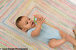 Infant boy age 6 months on back closeup holding toy transferring it hand to hand