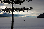 Idaho, Nordman, Priest Lake.  Frozen and snow covered Priest lake in the filtered morning light on Reeder Bay.