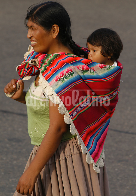 Una indigena aymara lleva su bebe a la antigua usanza cargado en la espalda en Santa Cruz de la Sierra.+indio+ *An Aymara indian carries her baby at her shoulders in Santa Cruz de la Sierra.