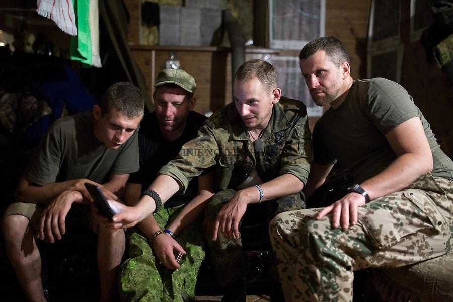 UKRAINE, Pisky: Dan and his comrades are watching a video on his phone during the evening. If they are not on night mission, all the unit stay inside the rear base as snipers and shelling are more constant at night.<br /> <br /> UKRAINE, Pisky: Dans la soir&eacute;e, Dan et ses camarades regardent une vid&eacute;o sur son t&eacute;l&eacute;phone. S'ils ne sont pas en mission de nuit, ils doivent rester &agrave; l'int&eacute;rieur de la base arri&egrave;re car les tireurs d'&eacute;lite et  bombardements sont plus constants dans la nuit.