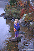Little girl in her rubber boots standing on a rock in the lake