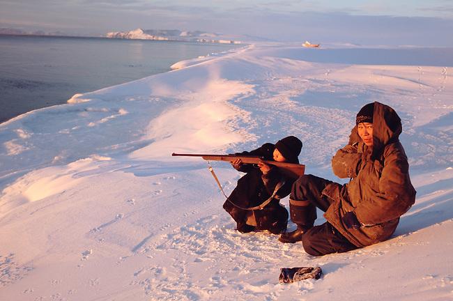 Two Chukchi boys, Larik Vukuchyvun (left) & Matvey Keytegin hunting seals from the snow covered shoreline. Dezhnovka, Chukotka Siberia