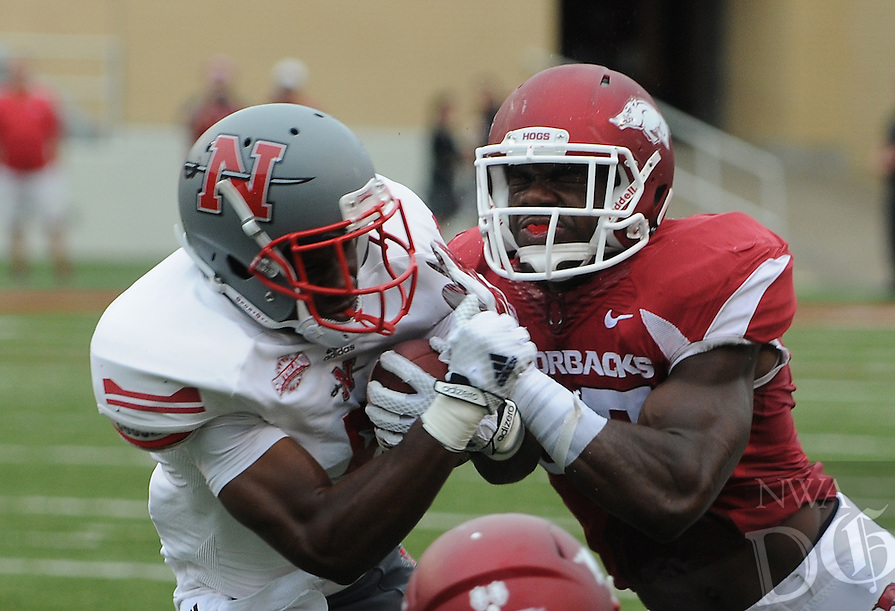 STAFF PHOTO ANTHONY REYES &bull; @NWATONYR<br /> Alan Turner, Razorbacks safety, delivers a bit hit against Tobias Lofton Nicholls State running back in the first quarter Saturday, Sept. 6, 2014 at Razorback Stadium in Fayetteville.