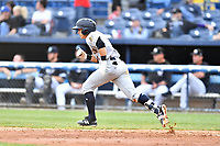 Charleston RiverDogs second baseman Kyle Gray (9) runs to first base during game one of a double header against the Asheville Tourists at McCormick Field on April 9, 2019 in Asheville, North Carolina. The Tourists defeated the RiverDogs 17-3. (Tony Farlow/Four Seam Images)