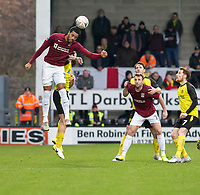 5th January 2020; Pirelli Stadium, Burton Upon Trent, Staffordshire, England; English FA Cup Football, Burton Albion versus Northampton Town; Vadaine Oliver of Northampton Town leaps above John Brayford of Burton Albion to head the ball - Strictly Editorial Use Only. No use with unauthorized audio, video, data, fixture lists, club/league logos or 'live' services. Online in-match use limited to 120 images, no video emulation. No use in betting, games or single club/league/player publications