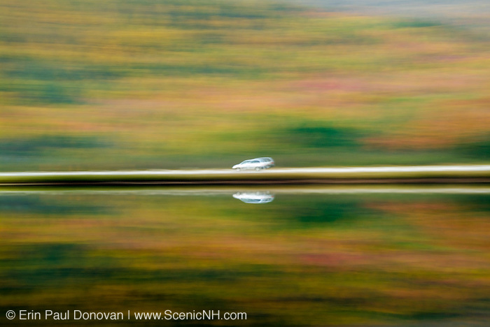 Motion blur - Reflection in Saco Lake of car traveling along Route 302 in the White Mountains, New Hampshire USA