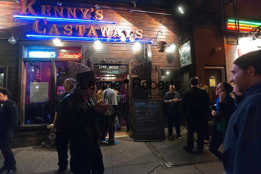 Patrons congregate outside Kenny's Castaways on Bleecker Street in Greenwich Village in New York on the last night that the club will be open, Monday, October 1, 2012. The historic venue, where music icons such as Bruce Springsteen and Patti Smith played, closed its doors citing the club's rent had more than doubled over the last five years. (© Richard B. Levine)
