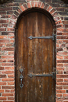 Arched rustic wooden door and walled garden.