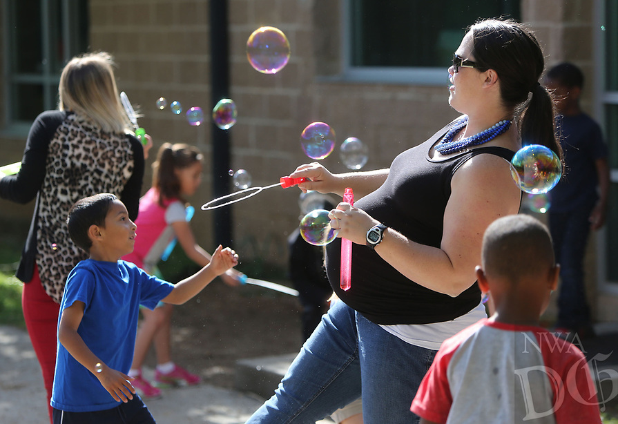 NWA Democrat-Gazette/DAVID GOTTSCHALK  Erica Powell, a kindergarten teacher at Owl Creek School, releases bubbles Tuesday, April 18, 2017, as students chase them during  a Soar Celebration at the school in Fayetteville. The school received a top ten ranking in the state from from Niche.com. Niche is a website that gathers comprehensive data about United State schools and neighborhoods. Students flew kites and released bubbles.